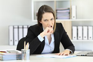 Angry executive sitting in a desktop