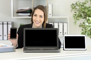 Happy office worker showing devices