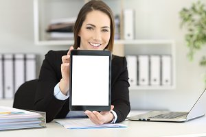Happy office worker showing a tablet