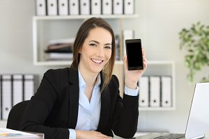 Happy office worker showing a phone