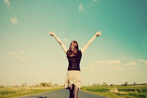 Woman standing with hands up on road