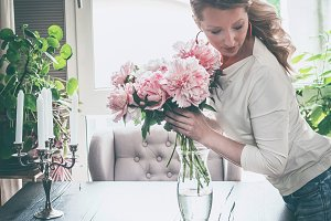 Women at home with peonies bunch