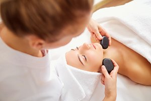 Massage face woman stone therapy.