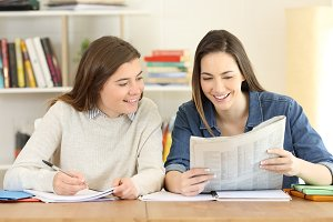 Two happy students reading news