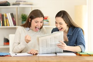 Two excited students reading news