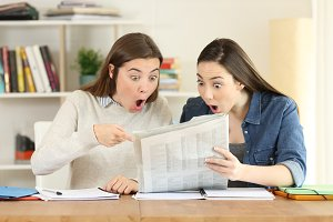 Two amazed students reading news