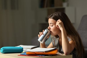 teen studying drinking energy drink