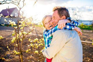 Senior couple hugging in spring garden, sunny nature