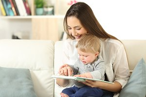 Baby and happy mother reading a book