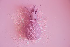Pink pineapple lying in glitters