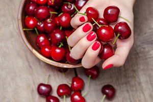 Female hand holding fresh cherries