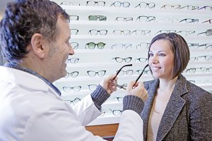 optician trying on glasses to a girl