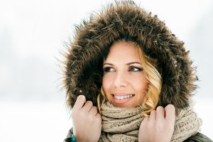 Woman in fur hood and scarf, snowy winter nature
