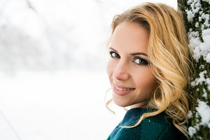 Smiling face of blond woman outside in winter nature