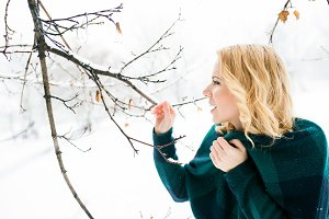 Blond woman in checked sweater outside in winter nature