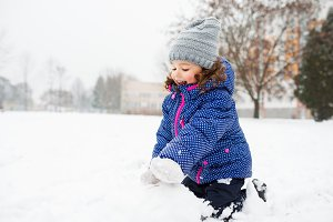 Little girl building a snowman in winter nature