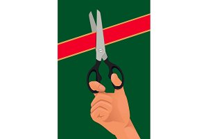 Hand with the scissors cut the red ribbon