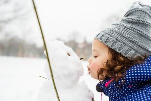 Little girl kissing a snowman in winter nature