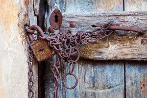 Rusty door lock and chain on an old door