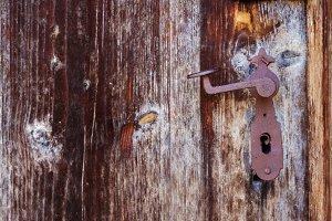 Rusty vintage door handle on an old wooden door