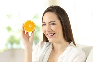 happy woman showing half orange