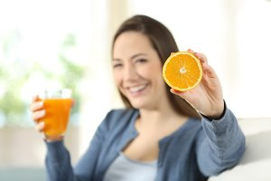 Happy woman showing a orange