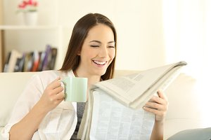Happy woman reading a newspaper