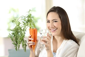 Happy woman holding carrots