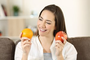 woman deciding between fruits