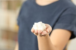 woman hand holding sugar cubes