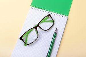Business accessories on desktop: notebook, diary, fountain pen, glasses. Macro with blur and soft focus.