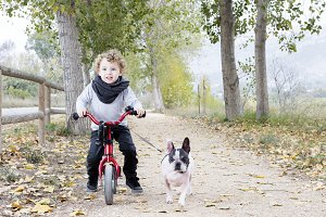 child riding bike with dog