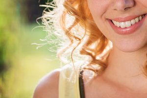 Unrecognizable blond woman, curly hair, green nature. Sunny summ