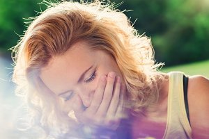 Blond woman laughing, holding mouth with hand . Sunny summer