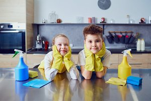 Smiling children do the cleaning in the kitchen