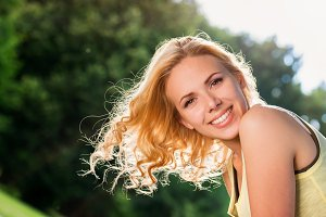 Blond woman, flipping curly hair. Sunny summer nature.