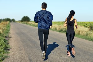 woman and man running rural road