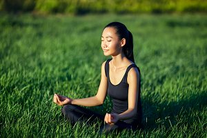 fitness woman meditating on grass