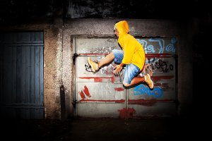 Man jumping against graffiti wall