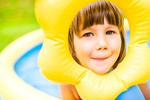 Little girl having fun in the garden swimming pool.