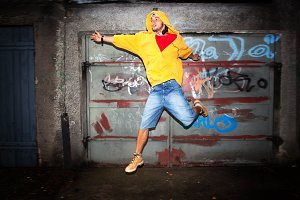 Jumping man against graffiti wall