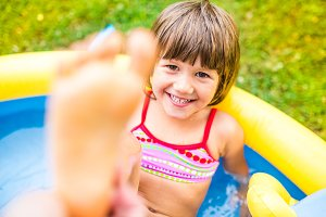 Little girl having fun in the garden swimming pool.