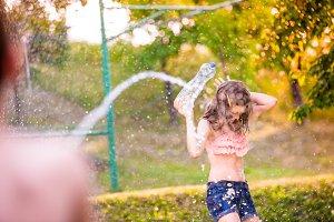 Unrecognizable boy splashing girl with water gun, sunny summer