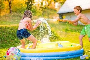 Boy splashing girl with water gun, garden swimming pool