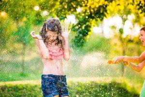 Boy splashing girl with water gun, sunny summer garden