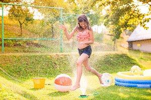 Girl running above a sprinkler, sunny summer back yard