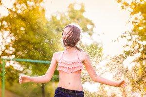Girl in bikini dancing at the sprinkler, summer garden