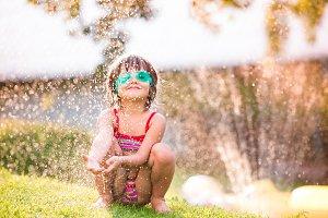 Cute girl crouching under the water splashing from sprinkler