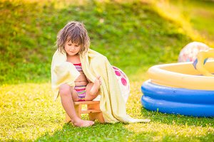 Girl wrapped in towel sitting by the swimming pool