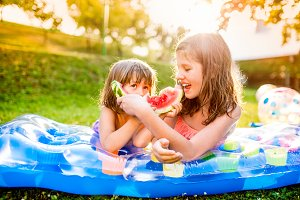Two cute girls eating watermelon in sunny summer garden
